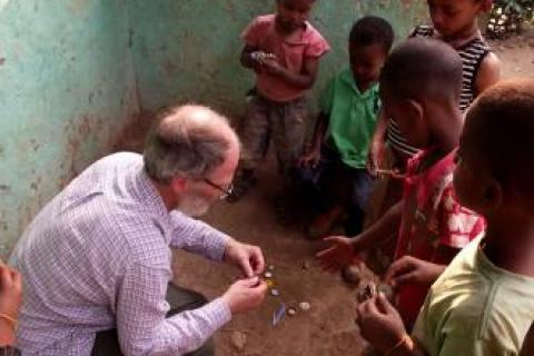 Ian Butler showing a child how to make a toy