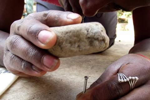 Hammering a nail with a stone